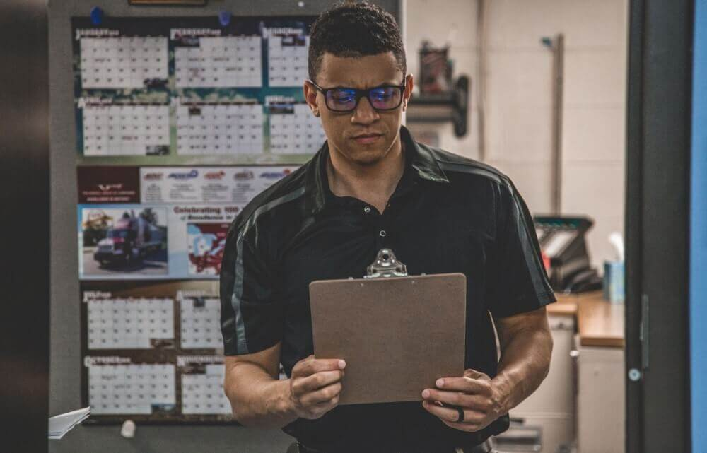 Man holding clipboard inside warehouse for inspection