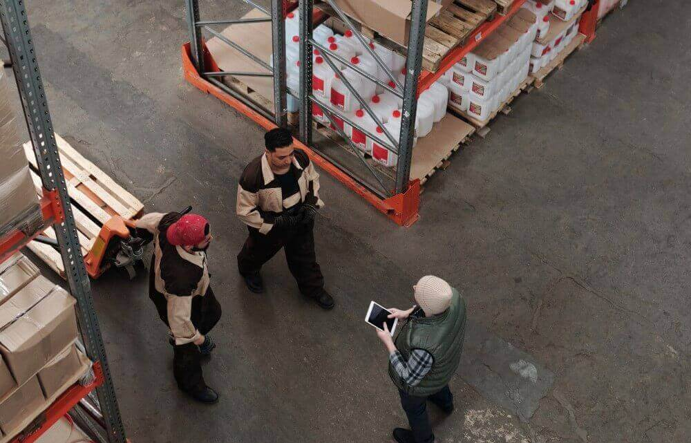 Men working in a warehouse providing training to the workers